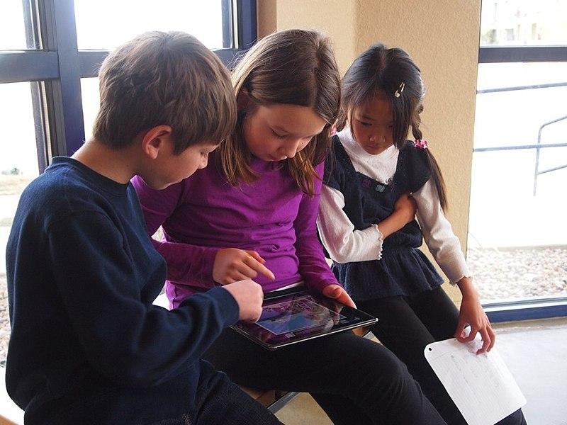 Kinder spielen auf iPad - Schule wird inklusiver
